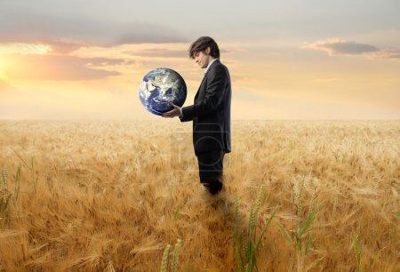 Photo pour Homme d'affaires debout sur un champ de blé et tenant la Terre - image libre de droit