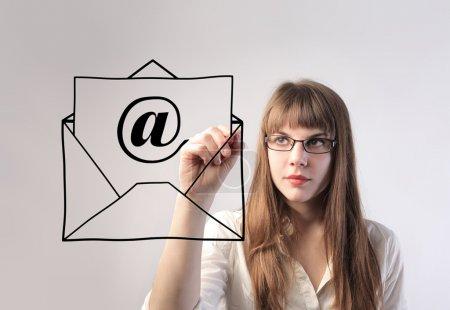 Photo pour Femme d'affaires dessinant une enveloppe avec un e-mail signe - image libre de droit