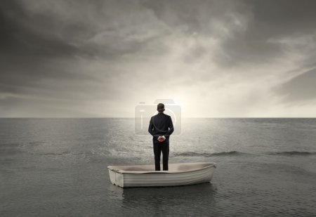 Photo for Businessman standing on a boat and observing the horizon - Royalty Free Image