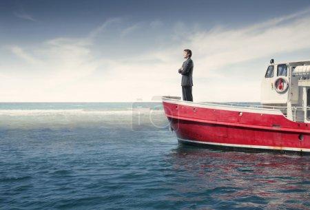 Photo pour Homme d'affaires, debout sur un bateau en mer - image libre de droit