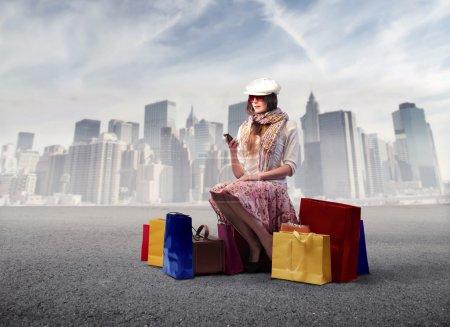 Photo pour Belle femme assise sur une rue de la ville entourée de nombreux sacs à provisions avec paysage urbain en arrière-plan - image libre de droit