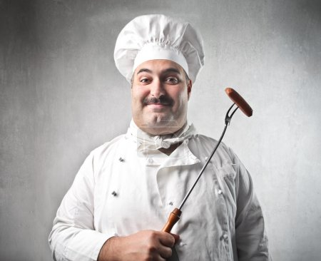 Photo for Smiling cook holding a sausage on a fork - Royalty Free Image