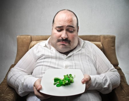 Photo for Sad fat man looking at his dish containing barely salad - Royalty Free Image