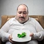 Sad fat man looking at his dish containing barely ...