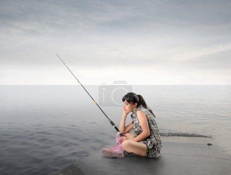 Photo pour Jeune femme assise sur une jetée et de pêche - image libre de droit