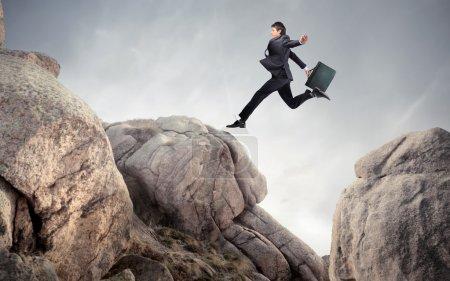 Foto de Empresario saltando de una roca a otra - Imagen libre de derechos