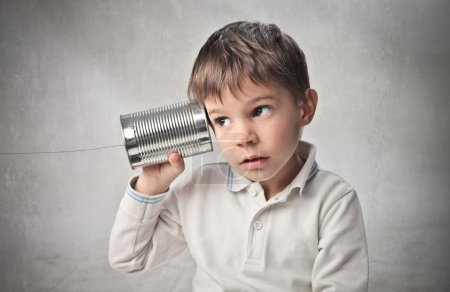 Photo pour Child talking on a telephone made with a can and a string - image libre de droit