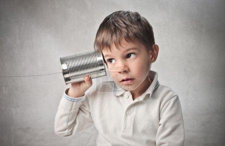 Photo pour Enfant parlant un téléphone fait avec une canette et une chaîne - image libre de droit