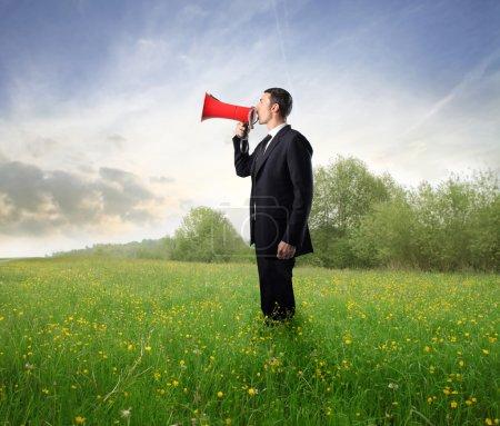 Photo pour Homme d'affaires sur une prairie verte en utilisant un mégaphone - image libre de droit