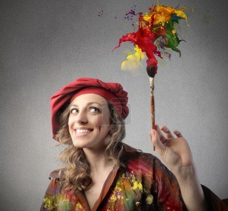 Foto de Sonriente mujer pintor llenando el aire con colores - Imagen libre de derechos