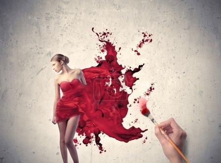Photo pour Les mains de l'homme peinture la robe d'une belle femme - image libre de droit