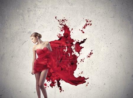 Photo pour Belle femme avec sa robe de fusion en peinture rouge - image libre de droit