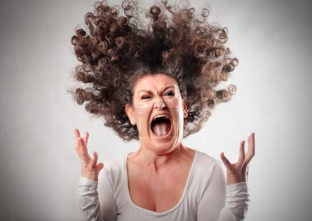 Photo for Very angry woman screaming her hair up in the air - Royalty Free Image
