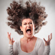 Very angry woman screaming her hair up in the air...
