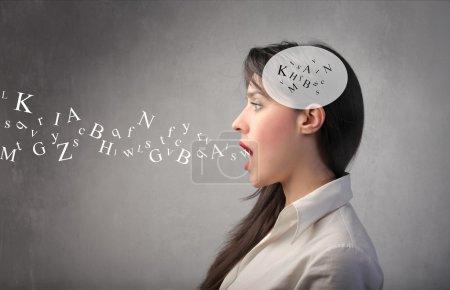 Photo pour Jeune femme parlant et lettres de l'alphabet sortant de sa bouche et la tête - image libre de droit