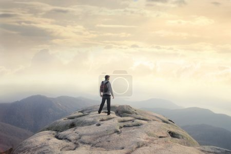 Photo for Man standing on a peak over the mountains - Royalty Free Image