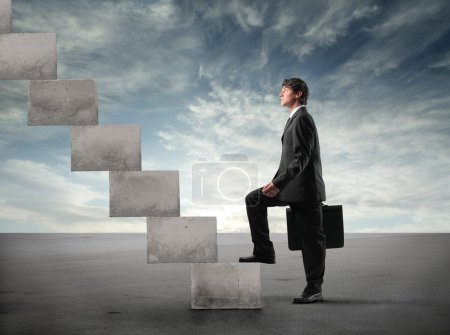 Photo for Young businessman stepping up a staircase - Royalty Free Image