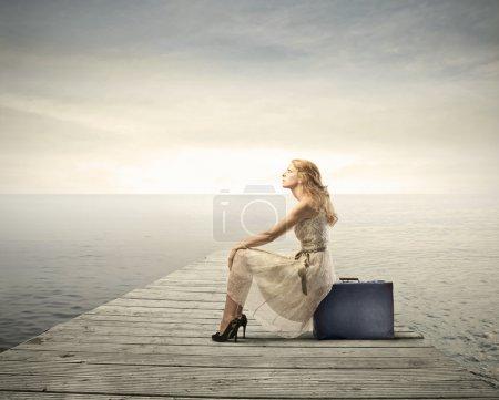 Photo pour Belle femme assise sur une valise sur un quai - image libre de droit