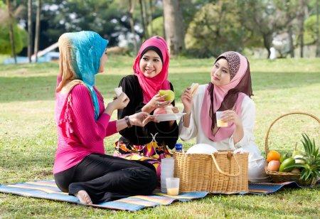 Photo pour Jeune femme musulmane portant une écharpe tout en se relaxant et en mangeant avec des amis dans le parc - image libre de droit