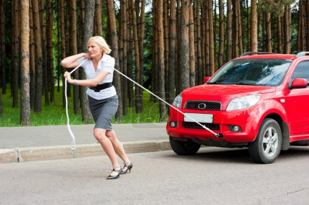 Photo for Blonde girl pulls a broken car with a rope - Royalty Free Image