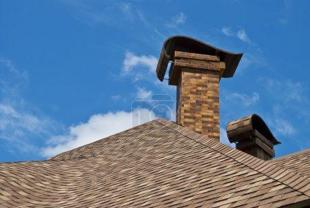 Photo pour Le toit de la maison avec deux cheminées dans la nouvelle conception contre le ciel bleu avec des nuages. - image libre de droit