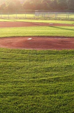 Photo pour Un terrain de baseball, monter dans la lumière matinale. - image libre de droit