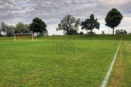 Photo for A cloudy unoccupied soccer field with trees in the background. (HDR photograph) - Royalty Free Image