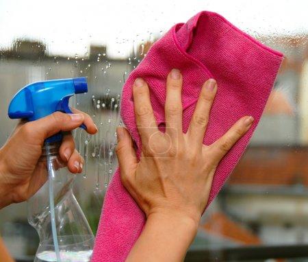 Photo pour Jeune femme mains sur la vitre de nettoyage d'un verre - image libre de droit