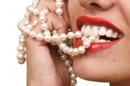 Photo pour Sourires de femme montrant les dents blanches, tenant un collier nacre dans la bouche, dents soin concept - image libre de droit