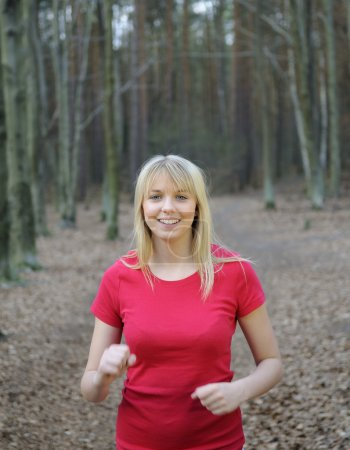 Beautiful young blond woman jogging in the forest...
