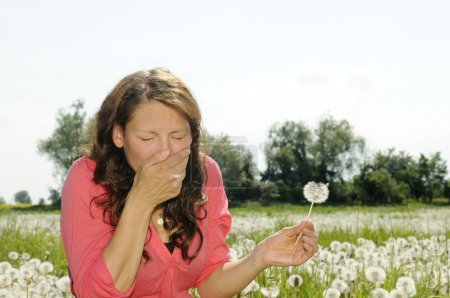 Young woman sneezes on a flower meadow