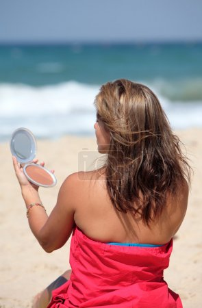 Young tanned woman putting make up on whilst on the beach