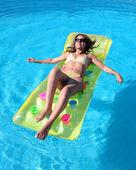 Atraktivní, štíhlá mladá dáma na nafukovací Lehátko na swimmi