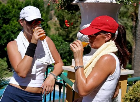 Two young, fit, healthy, tanned women having a drink after a hot