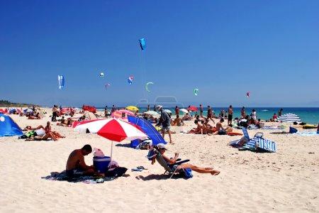 Photo pour Plage de sable blanc, ensoleillée et pleine de bains de soleil et de kitesurfeurs en été à Tarifa, Espagne - image libre de droit