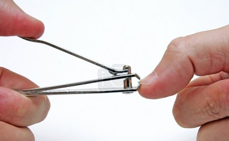 Close up of person cliiping finger nails with metal clippers.