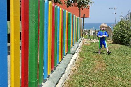 Photo pour Jeune garçon marchant à côté d'une clôture colorée en vacances en Espagne - image libre de droit