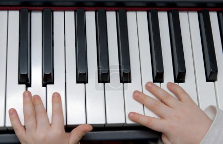 Young boys hands playing piano or keyboard
