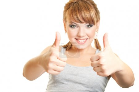 Smiling young woman with thumbs up on white background