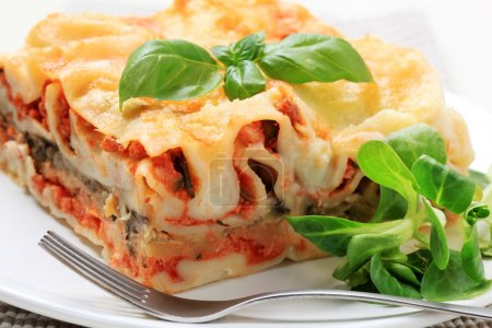 Photo for Portion of lasagna garnished with salad greens - Royalty Free Image