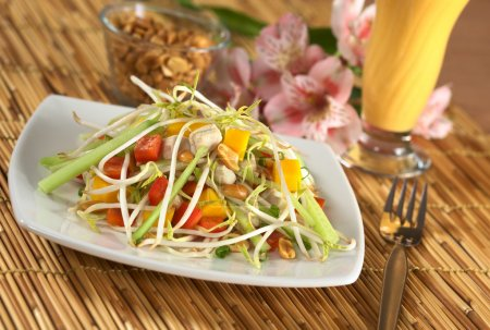 Photo for Fresh Asian salad with chicken, mango, cucumber, bean sprouts, red bell pepper and peanuts with mango juice in the back (Selective Focus, Focus on the top) - Royalty Free Image