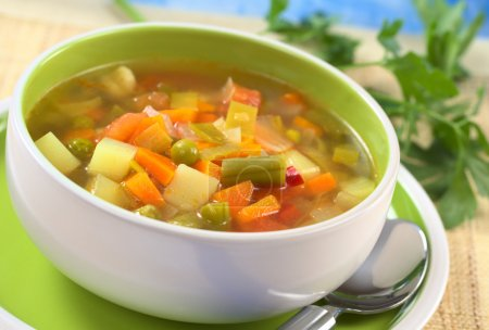 Photo for Fresh vegetable soup made of green bean, pea, carrot, potato, red bell pepper, tomato and leek in bowl with parsley in the back (Selective Focus) - Royalty Free Image