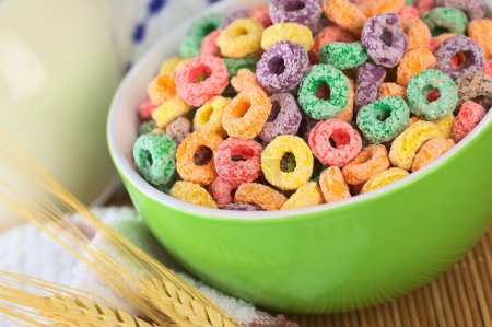 Photo for Colorful cereal loops with different fruit flavour in green bowl with milk in the back (Selective Focus, Focus one third into the bowl) - Royalty Free Image