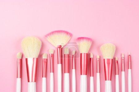 Photo pour Ensemble de pinceaux de maquillage blanc-rose sur fond rose. - image libre de droit