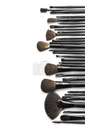Photo pour Ensemble de pinceaux à maquillage noir en ligne sur fond blanc comme frontière. - image libre de droit
