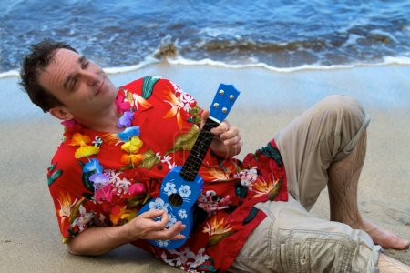 Photo for A man rest on the beach and sings while playing a ukelele in Maui, Hawaii. - Royalty Free Image