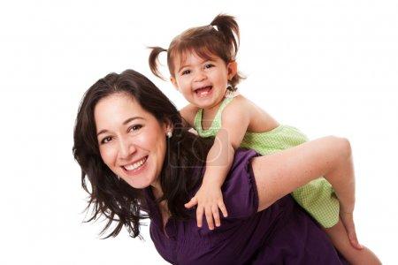 Foto de Muchacha del niño que ríe feliz jugando con mamá haciendo un divertido Caballito, aislado - Imagen libre de derechos