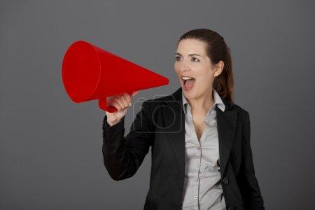 Photo pour Jeune femme d'affaires parlant à un mégaphone, sur un fond gris - image libre de droit