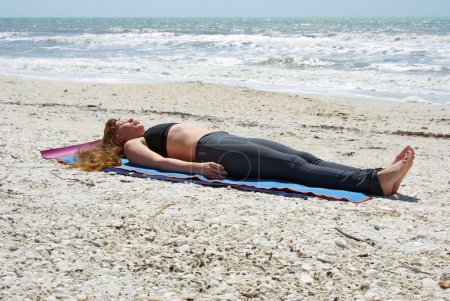 Woman doing yoga exercise on beach in Savasana or corpse pose