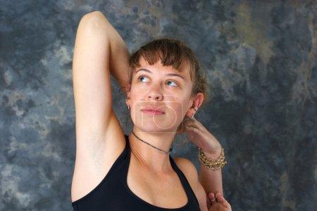 Photo pour Une jolie femme aux cheveux bruns fait posture de yoga Kapotasana ou King Pigeon Pose, gros plan sur le visage avec des perles de mala sur le poignet, les mains serrées derrière la tête et - image libre de droit